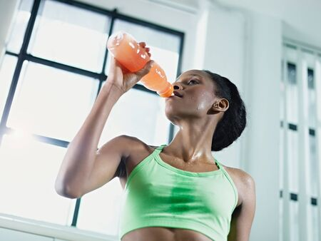 young african american woman in sportswear with energy drink in gym. Horizontal shape, waist up, low angle view photo