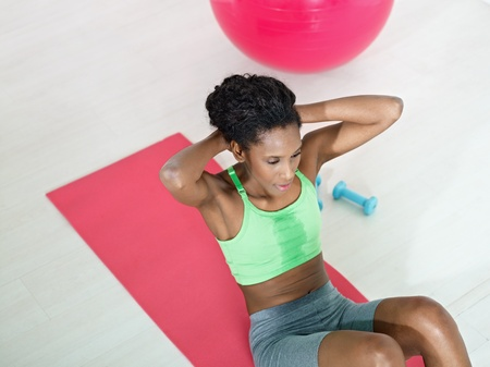 young african american woman in green sportswear exercising abdominals on pad in gym. Horizontal shape, high angle view, copy space photo