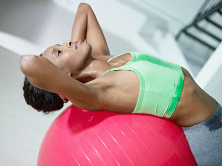 young african american woman in green sportswear exercising abdominals on fit ball in gym. Horizontal shape, side view, waist up photo