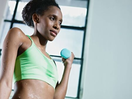 young african american woman in green sportswear doing weight lifting in fitness club. Horizontal shape, side view, copy space photo