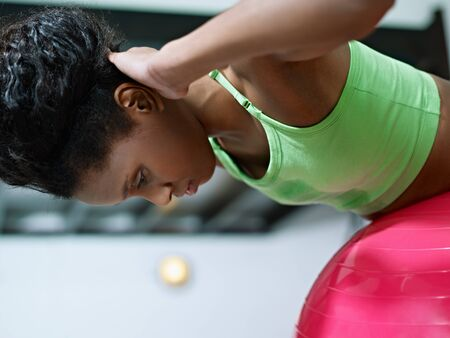 young african american woman in green sportswear exercising back muscles on fit ball in gym. Horizontal shape, side view, copy space Stock Photo - 8843304