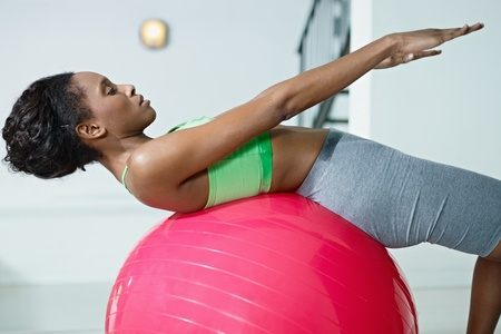 young african american woman in green sportswear exercising abdominals on fit ball in gym. Horizontal shape, side view, three quarter length photo