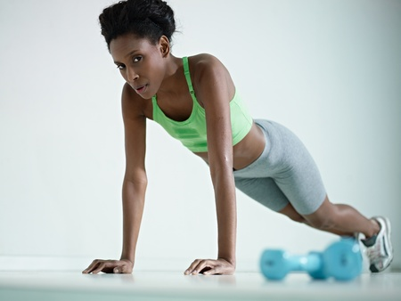 young african american woman in green sportswear exercising with pushups in fitness club, looking at camera. Horizontal shape, side view, copy space photo