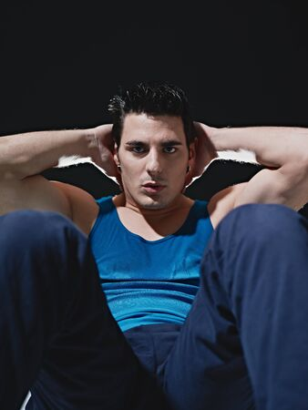 abdominals: young adult caucasian male in blue sportswear exercising abdominals on black background, looking at camera. Vertical shape, front view, copy space