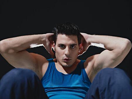 ropa deportiva: joven cauc�sico macho adulto en ropa deportiva azul ejercicio abdominales sobre fondo negro, mirando la c�mara. Copiar de forma horizontal, vista frontal, espacio
