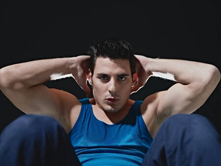 sportruházat: young adult caucasian male in blue sportswear exercising abdominals on black background, looking at camera. Horizontal shape, front view, copy space