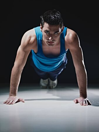 Young caucasian male in sportswear doing push ups on black background. Vertical shape, front view, copy space photo