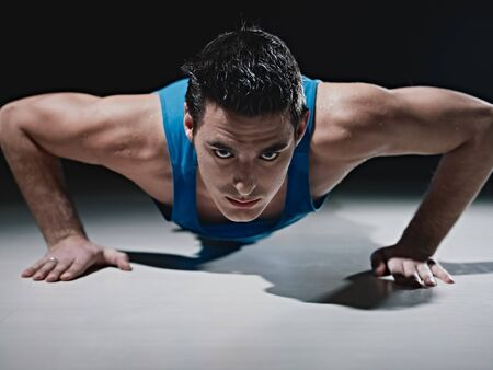 Young caucasian male in sportswear doing push ups on black background. Horizontal shape, front view, copy space photo