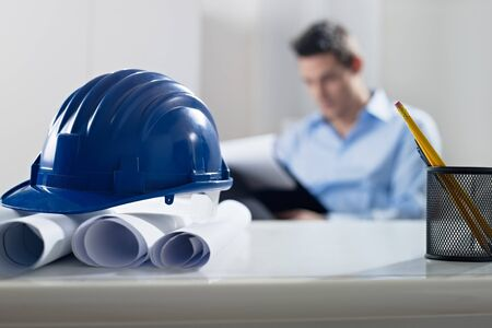engineering: adult caucasian male architect examining documents. Focus on blueprints and hardhat in foreground. Horizontal shape, front view