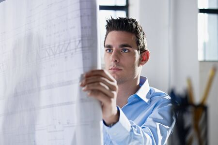 architect office: adult caucasian male architect examining blueprints. Horizontal shape, head and shoulders, side view