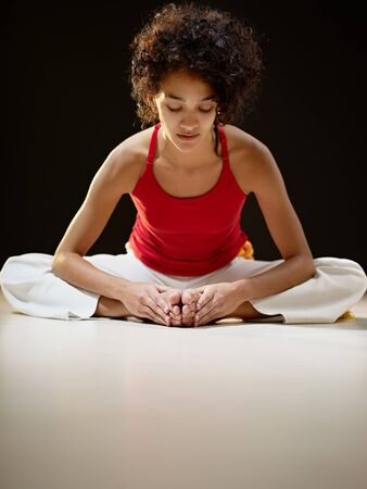 bending: portrait of young adult latin american female sitting on white floor doing yoga exercise. Vertical shape, full length, front view, copy space