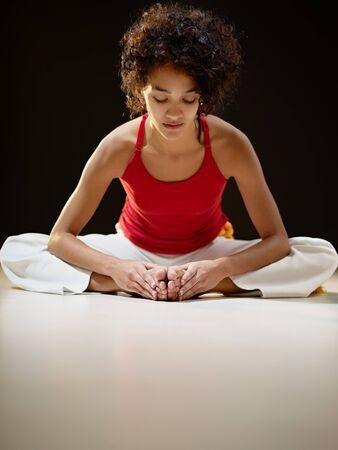 굽힘: portrait of young adult latin american female sitting on white floor doing yoga exercise. Vertical shape, full length, front view, copy space