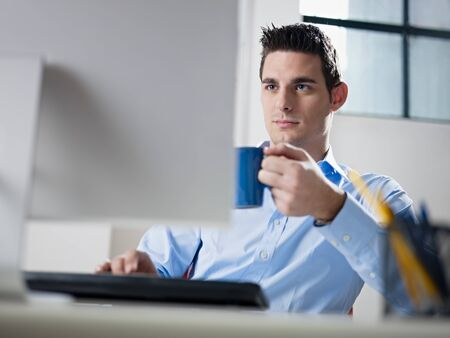 typing man: mid adult caucasian male business man looking at computer screen and holding blue coffee cup. Horizontal shape, waist up, front view