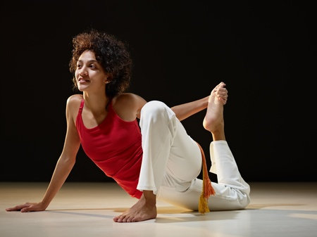 contortionist: portrait of young adult latin american female doing yoga exercise in gym. Horizontal shape, full length, side view, copy space