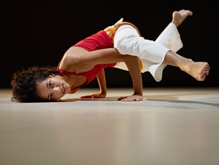 portrait of young adult latin american female doing yoga and capoeira in gym. Horizontal shape, full length, side view, copy space photo