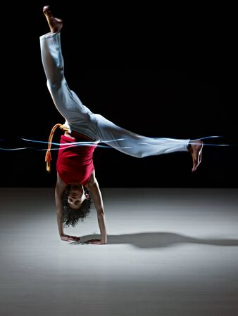 young adult latin american female handstanding and doing capoeira kick in gym, with streaks of led lights on waist. Vertical shape, full length, front view, copy space photo