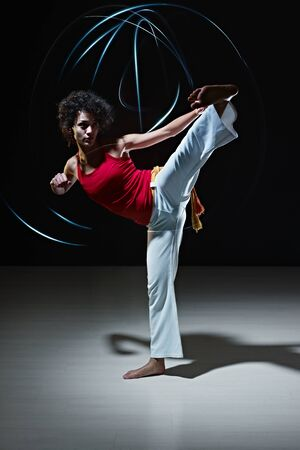 young adult latin american female doing capoeira side kick in gym, with streaks of led lights on top. Vertical shape, full length, front view, copy space photo