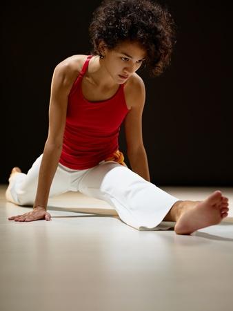 굽힘: portrait of young adult latin american female doing yoga and stretching exercise in gym. Vertical shape, full length, front view, copy space