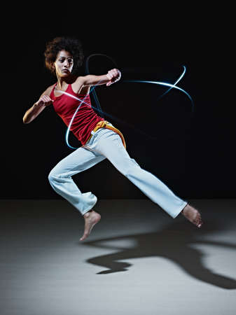 young adult latin american female doing capoeira flying kick in gym, with streaks of led lights all around. Vertical shape, full length, front view, copy space photo