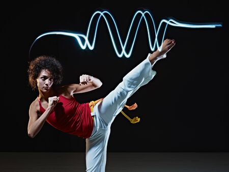 coup de pied: Jeune Am�rique latine femelle adulte faisant kick de c�t� de capoeira au gymnase, avec des stries de lumi�res LEDs sur le dessus. Forme verticale, pleine longueur, vue de face, espace de la copie