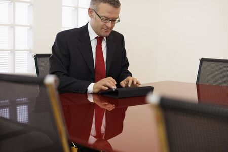 sala de reuniões: caucasiano, meio, adulto masculino digitação treinador de tablet pc na sala de reuniões. Forma horizontal, vista lateral, espaço da cópia