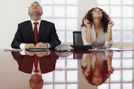 bored man: Bored businessman and secretary playing with pencil and having fun in office meeting room. Horizontal shape, front view, waist up Stock Photo