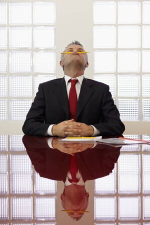 Frustrated mature businessman holding pencil between mouth and nose in office meeting room. Vertical shape, front view, waist up photo