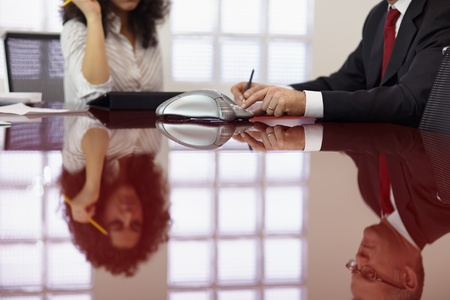 conference table: caucasian businessman and businesswoman in office meeting room, dialing on phone. Horizontal shape, side view Stock Photo