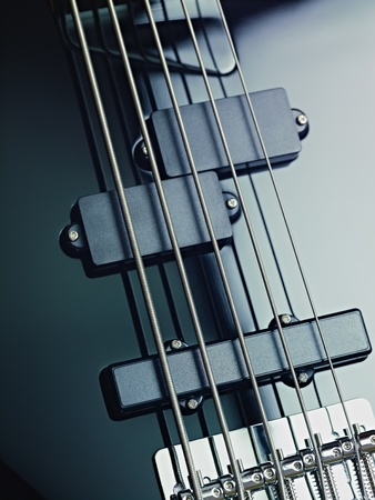 pickups: closeup of black five cords electric bass and pickups. Vertical shape, studio shot