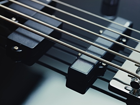 closeup of black five cords electric bass and pickups. Horizontal shape, studio shot photo