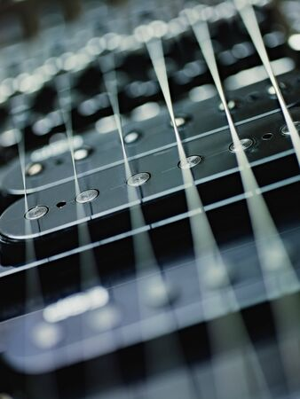 pickups: closeup of black electric guitar and pickups. Vertical shape, studio shot, selective focus Stock Photo