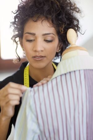 Young hispanic female dressmaker adjusting clothes on tailoring mannequin and smiling. Vertical shape, head and shoulders Stock Photo - 9124761