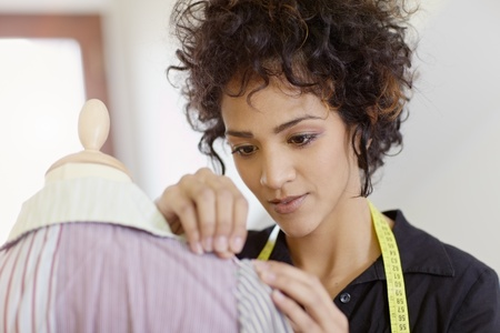 Young hispanic female dressmaker adjusting clothes on tailoring mannequin and smiling. Horizontal shape, head and shoulders Stock Photo - 9124762
