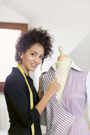 dressmaker: Young hispanic female dressmaker adjusting clothes on tailoring mannequin and smiling at camera. Vertical shape, side view, waist up Stock Photo