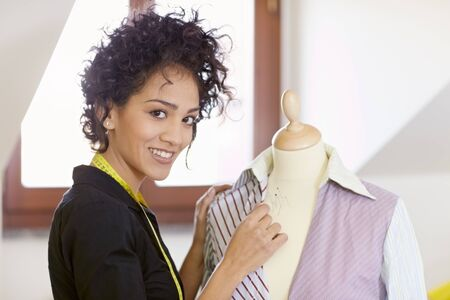 haute couture: Young hispanic female dressmaker adjusting clothes on tailoring mannequin and smiling at camera. Horizontal shape, side view, waist up
