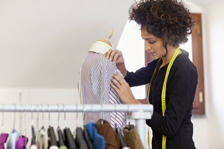 Young hispanic female dressmaker adjusting clothes on tailoring mannequin. Horizontal shape, waist up, copy space photo