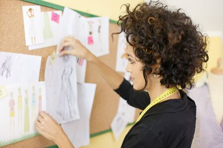 Young hispanic female dressmaker preparing show attaching drawings and sketches on board. Horizonta shape, side view, head and shoulders photo