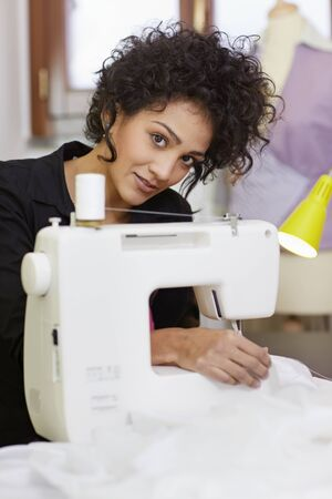 textile designer: Young hispanic female dressmaker using sewing machine and smiling at camera. Vertical shape, side view, waist up Stock Photo