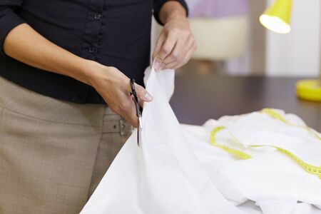 bridal gown: Young hispanic female dressmaker cutting white fabric for bridal gown. Horizontal shape, front view, selective focus Stock Photo