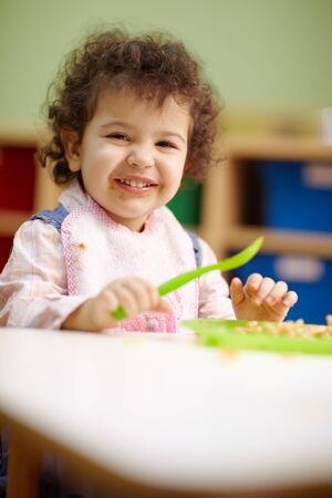dirty dishes: hispanic female preschooler eating pasta and smiling at camera. Vertical shape, waist up, copy space