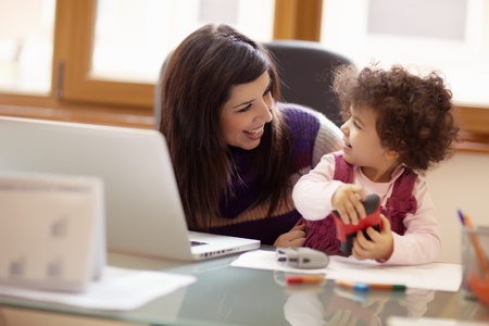 Mom and businesswoman working with laptop computer at home and playing with her baby girl. Horizontal shape, front view, waist up photo
