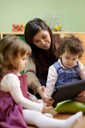 preschool children: Caucasian female educator and little girls reading fairy tale on touch pad computer in kindergarten