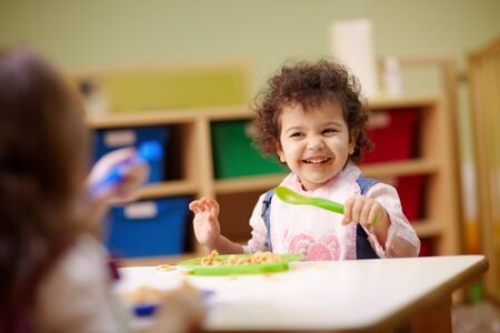 waist up: Caucasian and hispanic female preschoolers eating pasta and smiling. Horizontal shape, waist up, focus on background