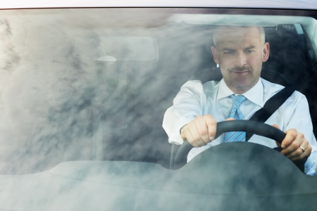 man driving: high angle view of caucasian mature business man with hands on steering wheel, looking away. Horizontal shape, waist up, copy space
