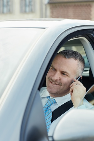 mature caucasian business man calling on the phone and smiling. Vertical shape, side view, head and shoulders photo