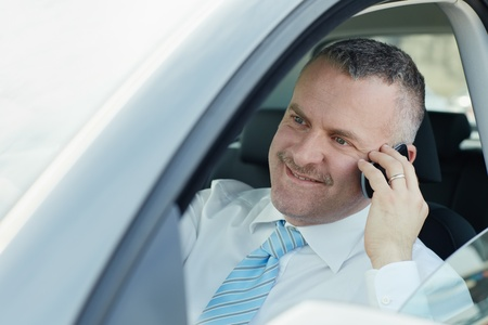 calling on phone: mature caucasian business man calling on the phone and smiling. Horizontal shape, side view, head and shoulders
