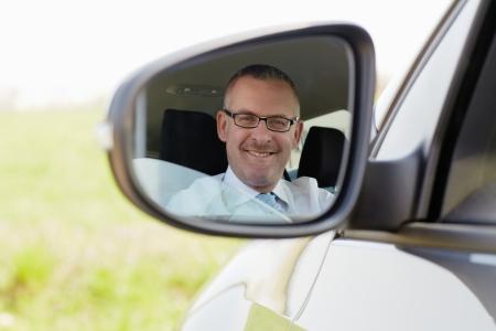 rear view mirror: hombre de negocios cauc�sica maduro mirando la c�mara a trav�s del espejo retrovisor. Hombros, cabeza y forma horizontal