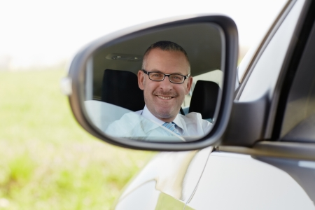 rear view mirror: mature caucasian business man looking at camera through rear view mirror. Horizontal shape, head and shoulders Stock Photo