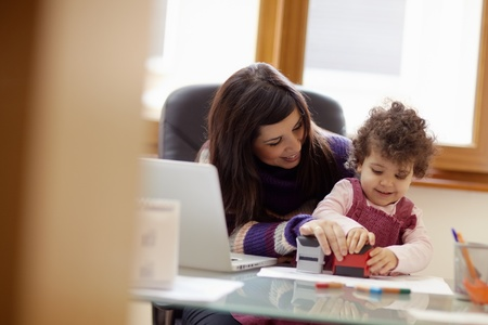 businesswoman working with laptop computer at home and playing with her baby girl. Horizontal shape, front view, waist up photo