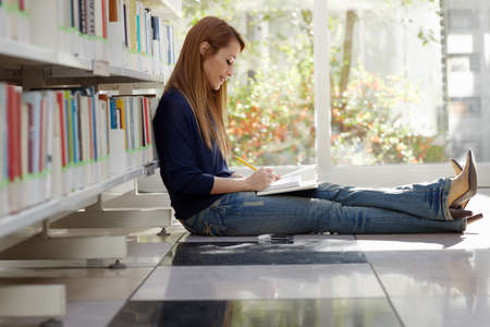 female college student sitting on floor in library, reading book and taking notes. Horizontal shape, side view, full length, copy space photo